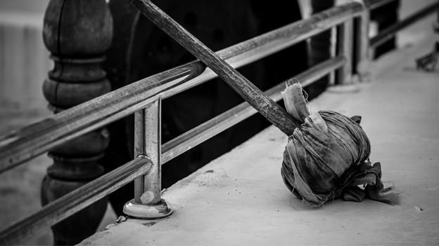 Gong-Schläger liegt an ein Geländer gelehnt. Dahinter zeichnen sich die Umrisse eines Gongs ab.