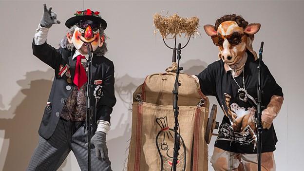 Zwei kostümierte Schnitzelbänggler präsentieren einen Bangg auf der Bühne.
