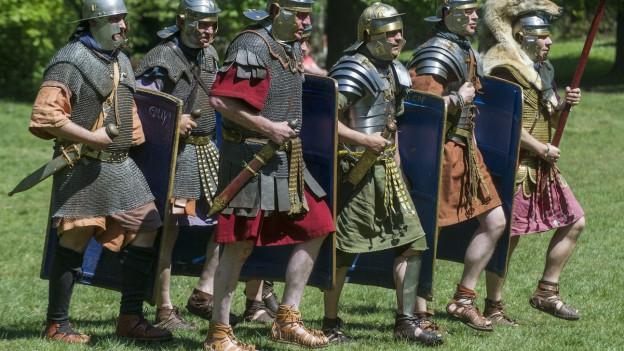 Sechs als Legionäre verkleidete Männer gehen mit Schild und Helm nebeneinander.