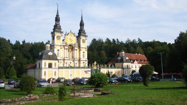 Eine Barockkirche mit hellgelb-weissen Aussenwänden und zwei Türmen.