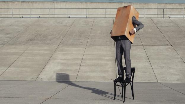 Mann steht auf einem Stuhl in einem Karton