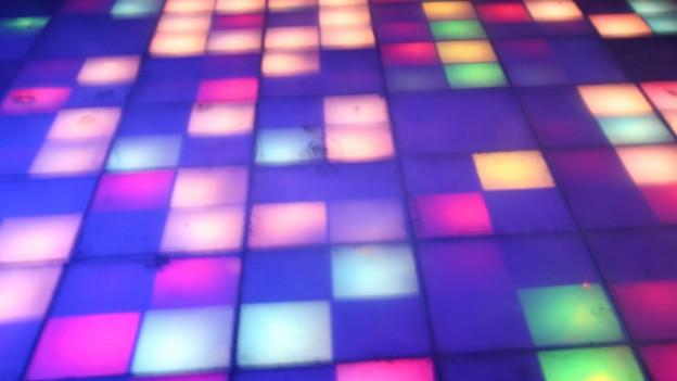 verschiedenfarbige leuchtende Bodenplatten in einer Diskothek.