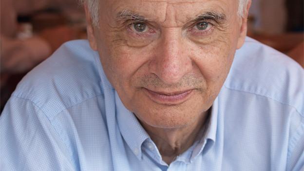 Porträt eines mannes mit hellblauem Hemd.