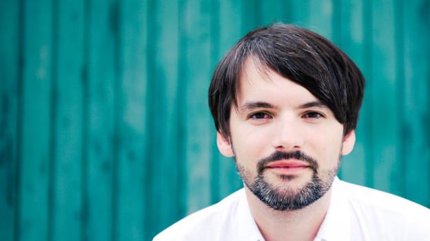 Ein junger Mann mit dunklen Haaren schaut in die Kamera vor blauem Hintergrund.
