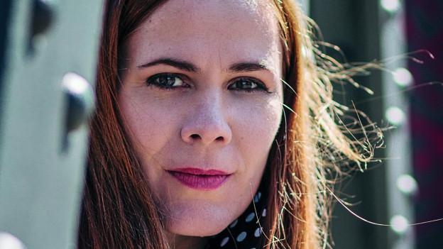 Eine Frau mit langen rötlichen Haaren blickt in die Kamera.