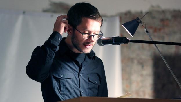 Ein Mann mit Brille in schwarzem Hemd steht vor einem Mikrophon.