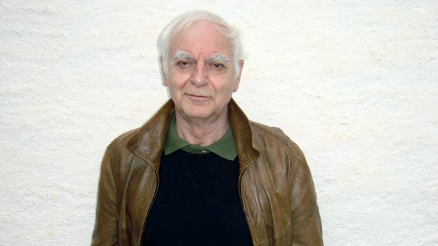 Ein älterer Mann mit grauen Haaren und brauner Lederjacke.