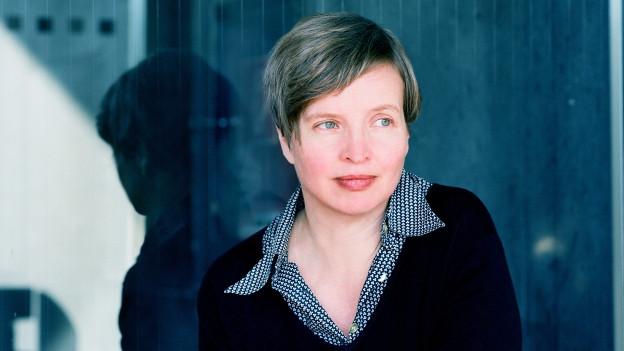 Eine Frau mit kurzen Haaren steht vor einem Fenster.