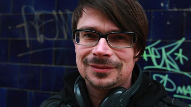 Ein Porträt von Jaroslav Rudiš. Er trägt Kopfhörer um den Hals.