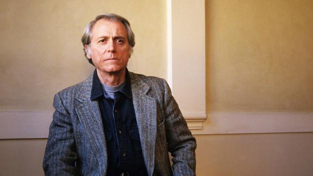 Porträt eines Mannes im grauen Anzug vor einer Treppe.