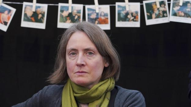 Eine Frau blickt in die Kamera, hinter ihr hängen Fotos