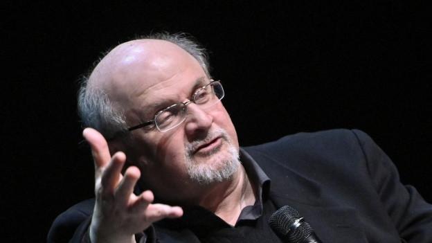 Ein grauhaariger Mann mit Brille gestikuliert