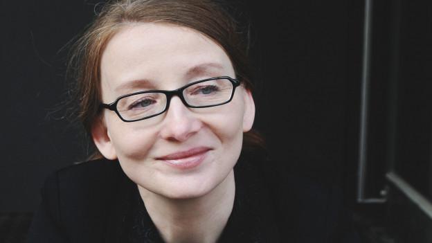 Eine Frau mit Brille blickt an der Kamera vorbei