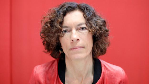 Frau mittleren Alters mit kinnlangen braunen Haaren vor rotem Hintergrund