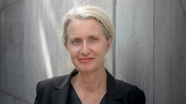 Frau mit grauen, zusammengebundenen Haaren und Brille sitzt vor einem Mikrofon mit einem Buch vor sich