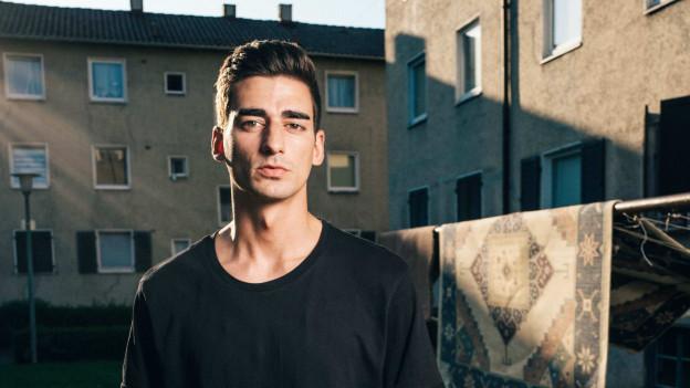 Junger Mann mit dunklen Haaren steht in einer Wohnsiedlung