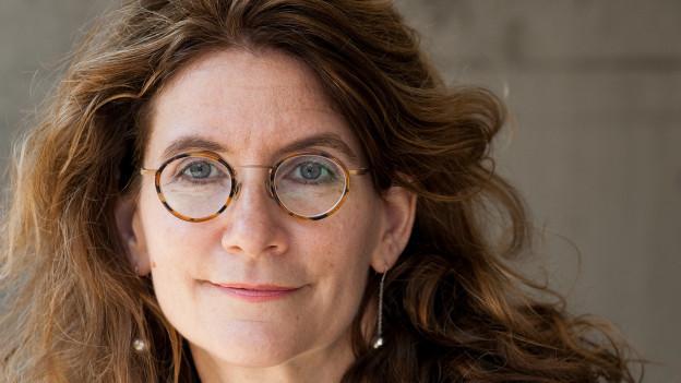 Frau mit langen, rotbraunen Haaren und runder Brille
