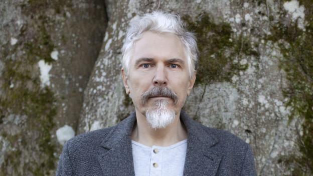 Mann mit grauen Haaren vor einer Steinmauer