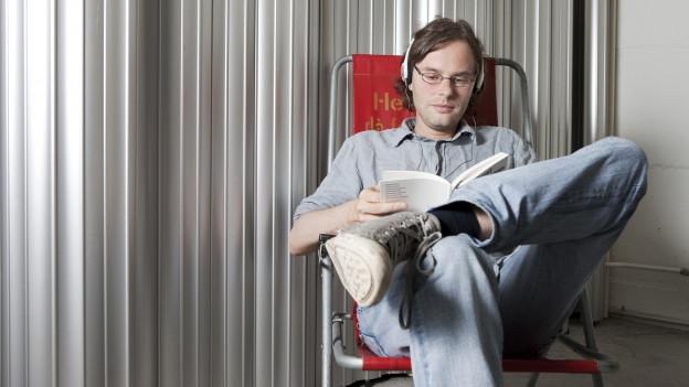 Ein junger Mann mit Brille trägt Kopfhörer und liest ein Buch während er in einem Campingstuhl sitzt.