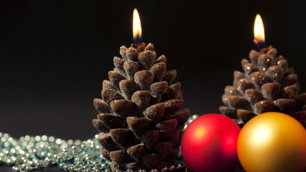Tannenzapfenkerzen und Weihnachtsschmuck