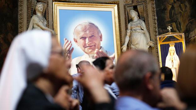 Johannes Paul II. Foto ist in einem Bilderrahmen. Im Vordergrund sind Nonnen.