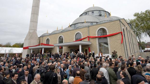 Eine Moschee in Deutschland mit einem Minarett und vielen Menschen davor.
