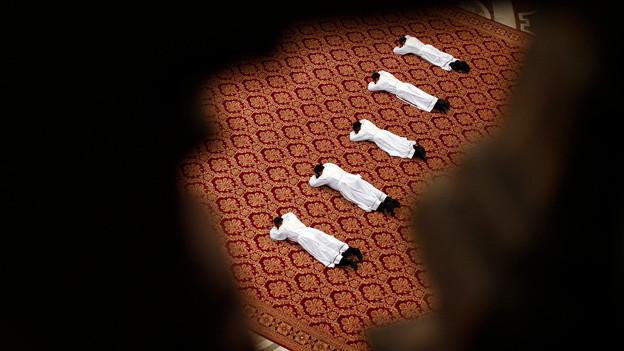 Prister liegen in weissen Gwändern auf dem Boden.