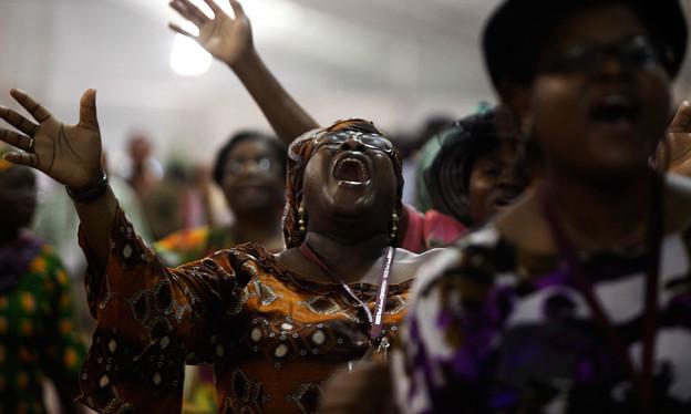 Eine dunkelhäutige Frau in einer Kirche, mit erhobenen Armen und geschlossen Augen, rufend.