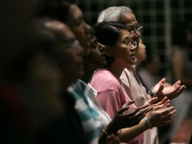 Menschen stehen in einer Reihe und beten, die Arme angewinkelt und die Handflächen nach oben zeigend.