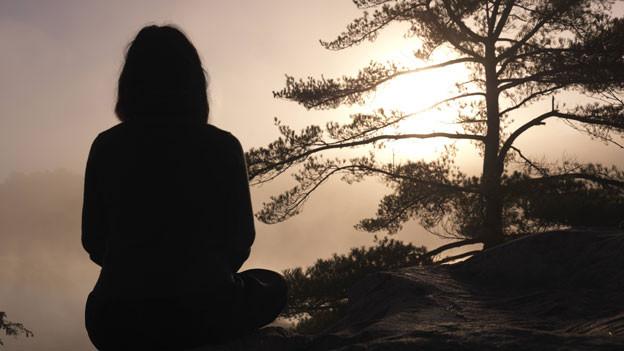 Eine Frau sietzt auf einem Felsen, im Hintergrund ein Baum und helles, nebliges Licht.
