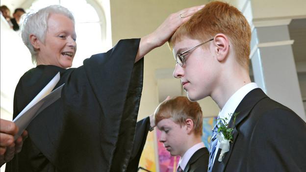 Ein Junge wird von einer Pfarrerin konfirmiert.
