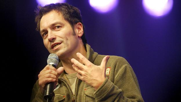 Ein Mann mit kurzen dunklen Haaren spricht in ein Mikrophon.