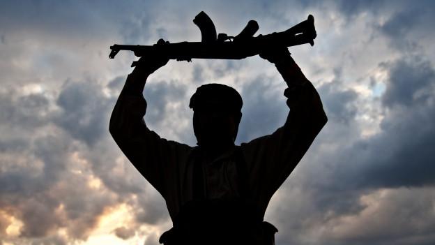 Die Silhouette eines Mannes mit Gewehr.