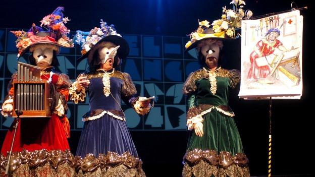 Drei als alte Damen verkleidete «Schnitzelbänkler» präsentieren auf der Bühne mit Handorgel und Helge.