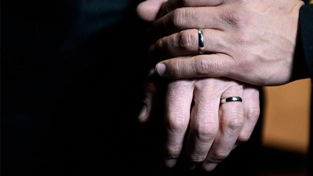 Nahaufnahme von den Händen zweier Männer mit Eheringen.