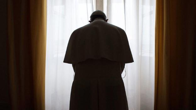 Der Papst betet. Man sieht seinen Rücken.
