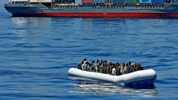 Im Meer ist ein grosses Schiff und davor ein kleines Boot voller Menschen zu sehen.