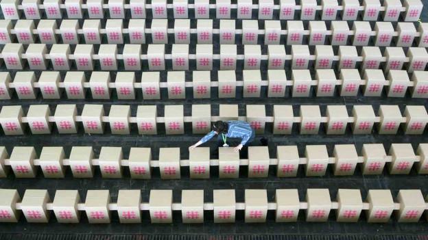 Frau stellt viele Pappstühle auf.