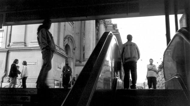 Schwarz-Weiss-Aufnahme einiger Menschen, die auf einer Rolltreppe, einem Treppenaufgang und dahinter unter freiem Himmel vor einer Kirche stehen.
