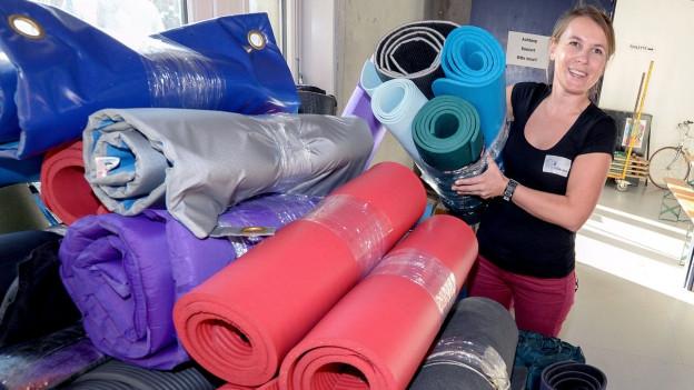 Eine Helferin der privaten Aktion «Tsüri hilft» stapelt Matten und Schlafsäcke.