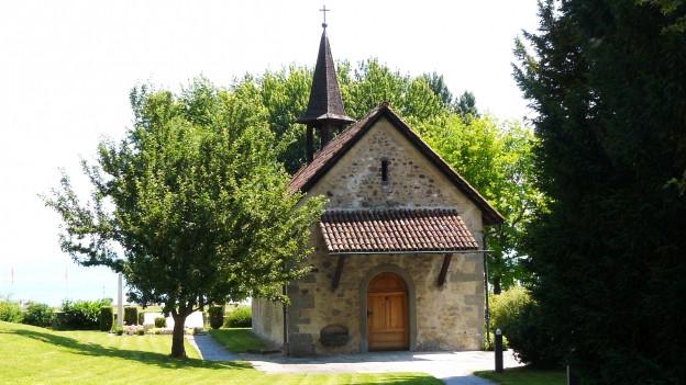 Kleine Kapelle umgeben von Bäumen.