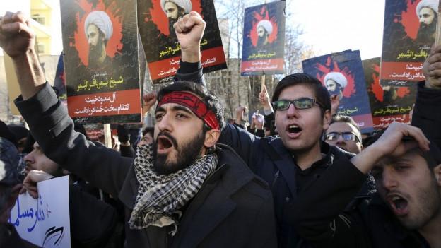 Demonstranten mit geballter Faust, die das Bild eines bärtigen Turbanträgers durcvh die Strasse tragen.