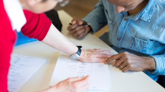 Eine Frau zeigt einem Mann ein Formular.