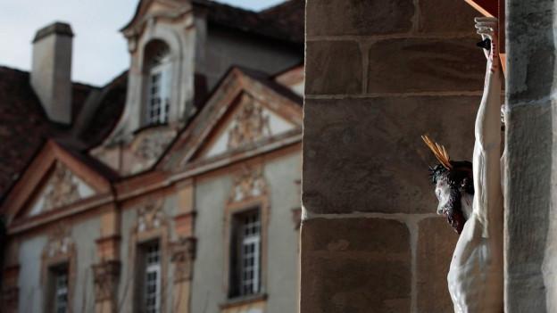 Jesus am Kreuz an einer Kirchenfassade.