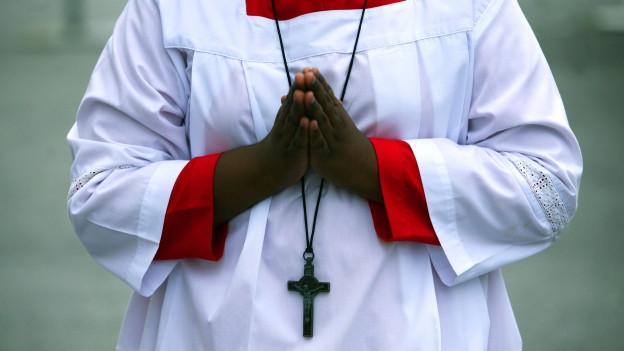 Symbolbild: Ministrant betet während dem Gottesdienst.