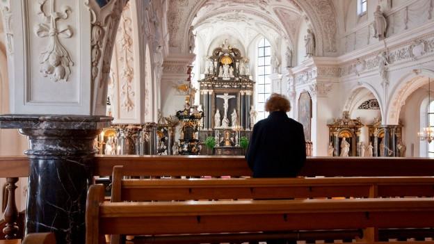 Symbolbild: Eine Frau betet in einer Kirche