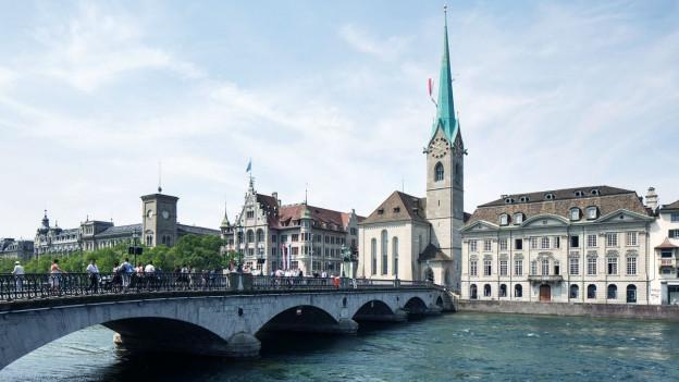 Fluss, über den eine Brücke führt. Am Ufer steht eine Kirche.