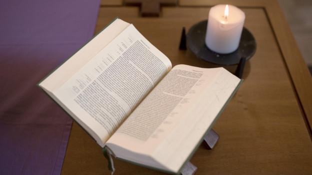 Eine Bibel und eine Kerze.