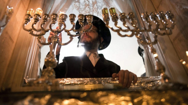Ein jüdischer Mann zündet Kerzen an.