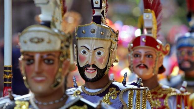 Menschen in den Philippinen tragen farbige Holzmasken zur Verehrung Jesus Christus